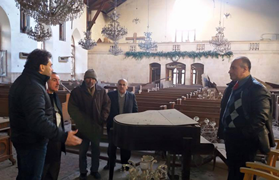 Rev. Selimian and community members assess the damage to the church. (Public Radio of Armenia)