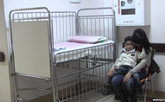 A child suffering from a respiratory virus and his mother wait in the hallway of Arabkir hospital. (Source: RFE/RL)