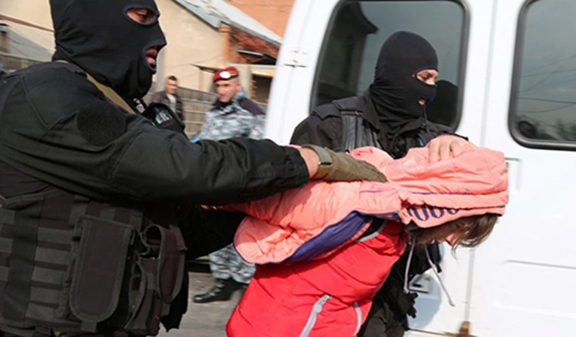 Security forces detain a woman in a raid on a house in Yerevan's Nork district on Nov. 25, 2015. (Source: RFE/RL)