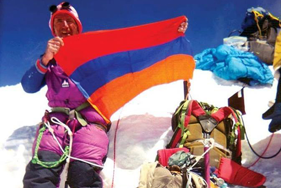Lev Sarkisov proudly holding the Armenian flag after a climb. (Source: Public Radio of Armenia)