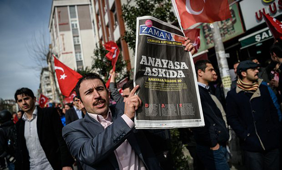 A protester holds a copy of Turkish newspaper Zaman during a demonstration in Istanbul on March 6. (Source: Ozan Kose/AFP/Getty Images)