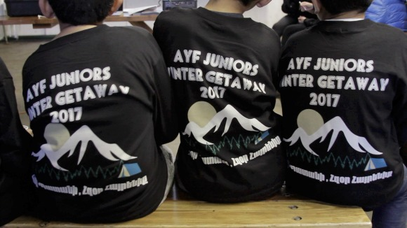 AYF Juniors with farewell gifted long sleeves that read Հզօր Պատանի, Հզօր Հայրենիք/Hzor Badani, Hzor Hayrenik/Strong Badani, Strong Fatherland