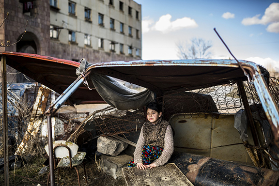 "Nine-year-old Suzanna sitting in a ""shelter"" made of old car rusty parts ten days after her father committed suicide (Photo: Yulia Grigoryants)"