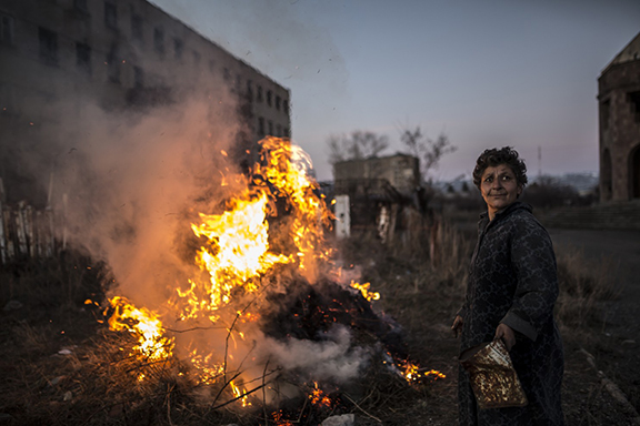 Karine, 57, launches a fire in between two buildings after winter. (Yulia Grigoryants)