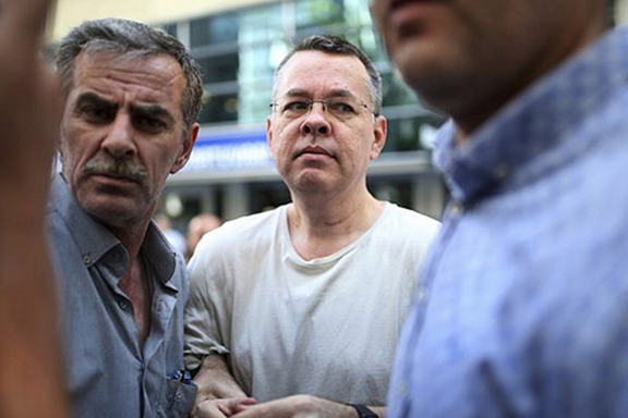 Turkish security officials escort Pastor Andrew Brunson (center) to his residence after being place on house arrest last week
