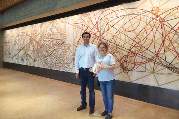 Christine Yesayan with the mural at the Gulbenkian Foundation's office is by Almada Negreiros