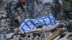 Emergency workers move the body of an 80-year-old women from the rubble of her house in Stepanakert, which was bombed by Azeri forces on Nov. 6