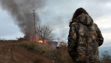 An Artsakh resident in Berdzor watches houses burn in the Lachin district before the handover to Azerbaijan (Tass photo)
