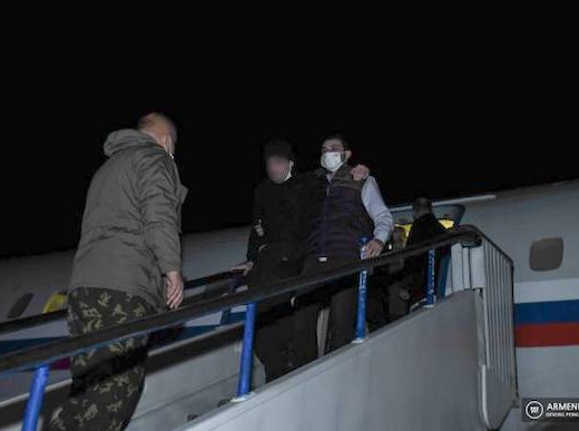 One of the five Armenian prisoners of war is being escorted off a plane that landed at Erebuni Airport on Jan. 28