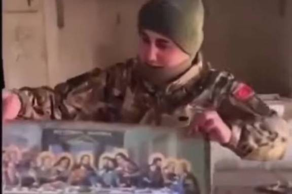 A screen capture showing an Azeri soldier defacing what appears to be a fresco of the Last Supper from a church in Mataghis