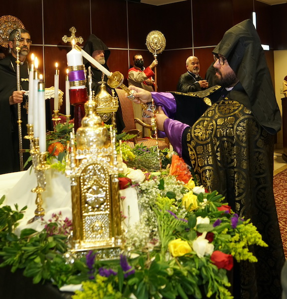 """Western Prelate Bishop Torkom Donoyan lights one of 250 candles in memory of martyrs, after announcing the """"Artsakh Heroes Families Fund"""""""