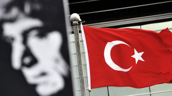 A poster bearing a picture of Hrant Dink and a Turkish flag are pictured in front of an Istanbul court