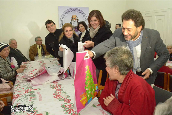 Rev. Haroutune Selimian distributes gifts t othe elderly of the Old Peoples Home in Aleppo (Source: Studio Venus)