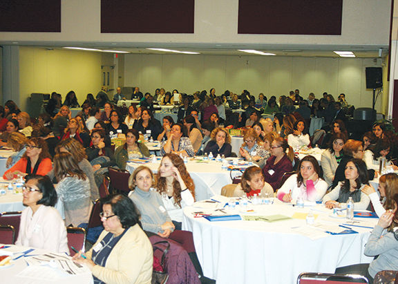 Educators listen attentively to the opening session of the conference