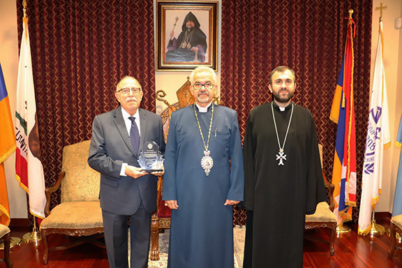 Prelate Archbishop Mardirossian awards Karamardian with a plaque, from l to r: Vice-Chair of Forty Martyrs Church of Orange County Board of Trustees Garbis Karamardian, Western Prelate Archbishop Moushegh Mardirossian, and Forty Martyrs Church Parish Pastor Reverend Karekin Bedourian