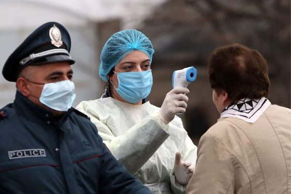 A healthcare workers takes a person's temperature on the street