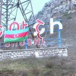 An Azerbaijani flag is draped over the sign identifying the city of Shushi